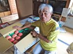 Suzuki-san sits next to a box of locally-grown peaches brought over by a neighbor. 鈴木さんは隣の人からもらった地元で生産されたももを見せています。